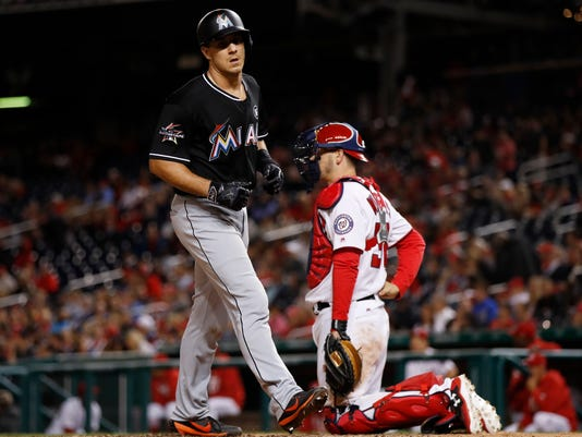 Miami Marlins catcher J.T. Realmuto (11) touches the home plate after hitting a homer while Washington Nationals catcher Matt Wieters, right, watches during the eighth inning of a baseball game against the Washington Nationals in Washington, Wednesday, April 5, 2017. The Nationals won 6-4. (AP Photo/Manuel Balce Ceneta)