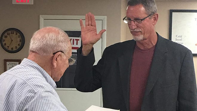 Ashland City Judge Bill Stinnett, left, swears in new City Council member Gary Norwood.