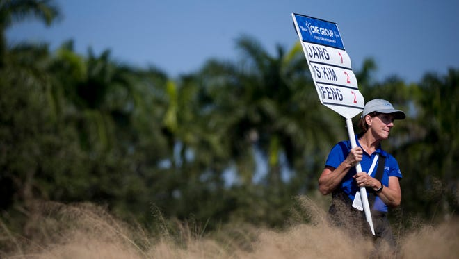 A volunteer holds up a sign with scores during the CME Group Tour Championship at Tiburon Golf Club Thursday, Nov. 17, 2016 in Naples.
