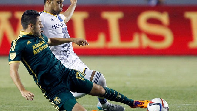 Portland Timbers midfielder Michael Nanchoff, left, tackles the ball away from Los Angeles Galaxy midfielder Kenney Walker during the second half of an MLS soccer game in Carson, Calif., Wednesday, June 24, 2015. The Galaxy won 5-0. (AP Photo/Alex Gallardo)
