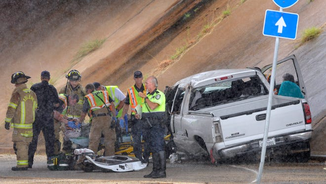 Rain falls as first responders strap an occupant of a pickup truck into a gurney Tuesday afternoon August 1, 2017 below the Winters Freeway overpass at Old Anson Road. The pickup had been pulling a trailer northbound when it lost control and ended up on the street.