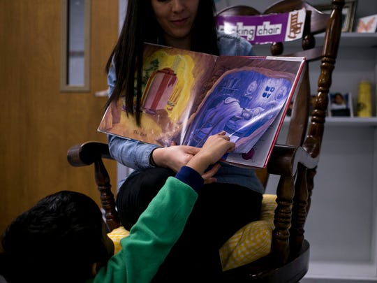 Sergio Hau, 6, points to a page in the book that his