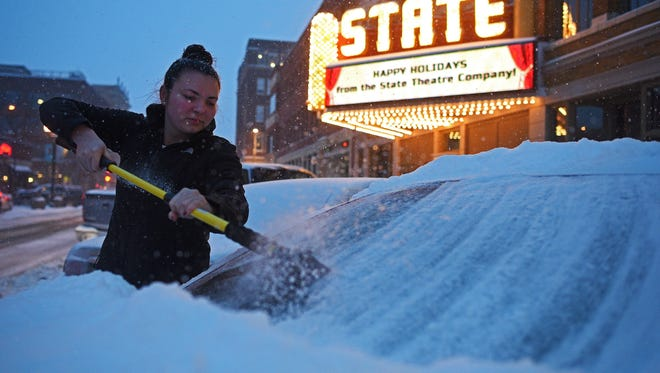Mya Baca, of Sioux Falls, brushes snow from her car during Friday's winter storm, Dec. 16, 2016, in downtown Sioux Falls.