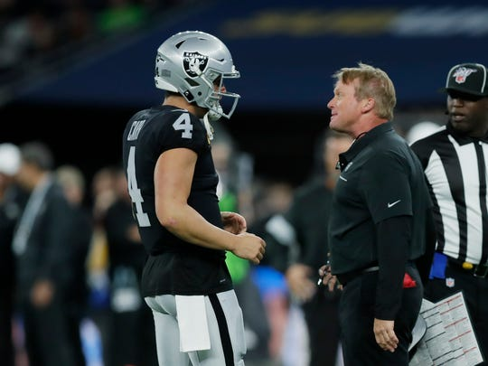 Oakland Raiders head coach Jon Gruden, front right, talks with quarterback Derek Carr (4) during the first half of an NFL football game against the Chicago Bears at Tottenham Hotspur Stadium, Sunday, Oct. 6, 2019, in London. (AP Photo/Kirsty Wigglesworth)