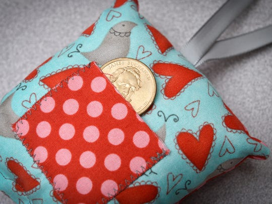 Rebecca Dombrovski, Rice, creates small pillows out of scraps of material shown Wednesday, July 11, for children who lose a tooth when staying at Anna Marie's Alliance.