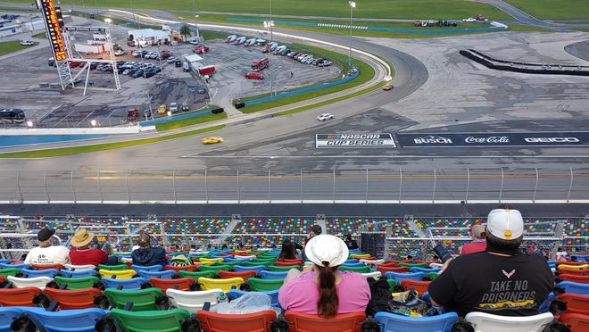 Spread-out fans watch cars dive into the infield road course at Daytona International Speedway during Saturday night's WeatherTech 240.