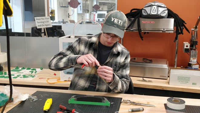Western Reserve Academy graduate Walker Larivee works on a medical face shield in WRA's Wang Innovation Center.