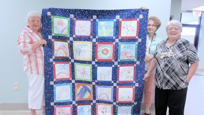 Noah's Ark Pre-School crayon-block quilt is displayed by Carol Lewis, Sue Schaufler and Margaret Wilburn.