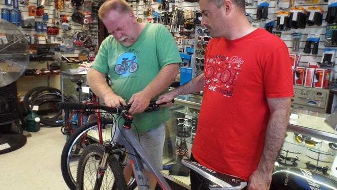 Randy Tooker, left, manager of the pv Bicycle Shop in Pleasant Valley, fits a cellphone holder to the handlebar of Liam Moran's mountain bike. Moran, of Astoria, Queens County, was on his way to ride bike paths in Pleasant Valley's Taconic-Hereford Multiple Use Area.