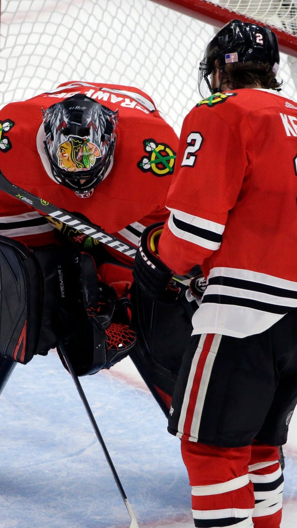 Chicago Blackhawks goalie Corey Crawford, left, looks