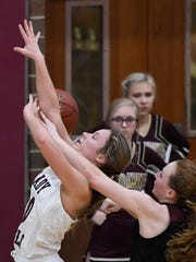 Henderson's Kaytlan Kemp (20) is fouled by Webster County's Marissa Austin (2) as the Henderson County Lady Colonels play the Webster County Lady Trojans in the Sixth District Tournament Championship at Colonel Gym in Henderson Tuesday, February 20, 2018.