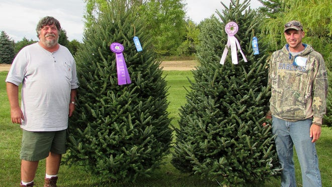 Dave Vander Velden, owner of Whispering Pines Tree Farm, stands with Chris Duffy, his employee. The farm's balsam fir won the Grand Champion award at the annual Wisconsin Christmas tree contest held near Deer Park in Northwest Wisconsin.