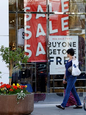 A shopper walks past a store advertising a sale Friday, July 3, 2015, in Emeryville, Calif.