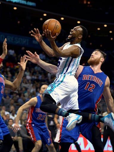 Charlotte Hornets' Kemba Walker, center, drives to