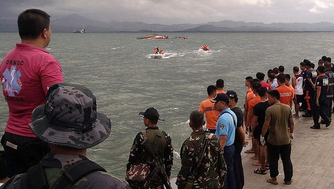 The capsized ferry boat, rear center, is approached by rescue workers in Ormoc city on Leyte Island, Philippines, Thursday, July 2, 2015.