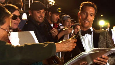 Actor Matthew McConaughey signs for fans during the red carpet arrivals at the 25th annual gala.