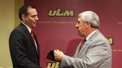 Wickstrom (left) shakes hands with Bruno (right) when he was hired as ULM athletic director in 2013.