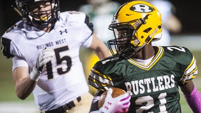 C.M. Russell High's Damien Nelson sprints with the ball, glancing behind at Billings West's Hugh Edward during the game at Memorial Stadium Thursday.