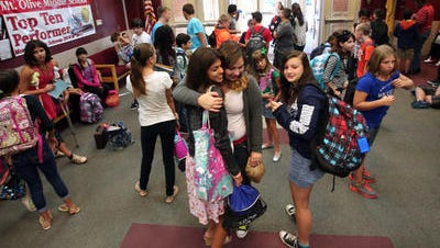 Sophia Lake (left), 13, is hugged by Sydney Garver, 13, prior to Mount Olive Middle School's first day of classes on Wednesday of last year.