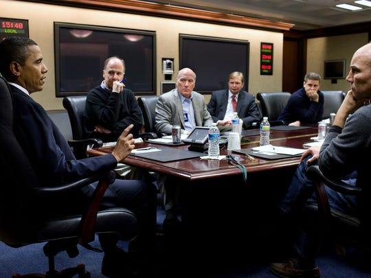President Barack Obama takes part in a conference call in the Situation Room of The White House concerning the shooting of Rep. Gabrielle Giffords in January 2011 as adviser Dan Pfeiffer looks on.