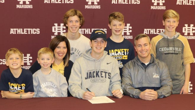 Holland Christian's Kaden Shook signs with Cedarville surrounded by his family.