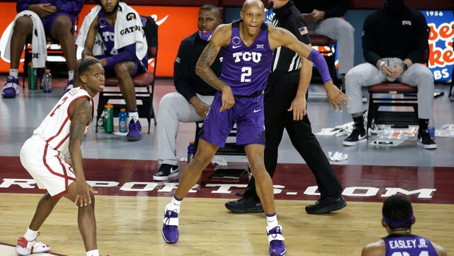 TCU's Mickey Pearson Jr. (2) passes the ball to Kevin Easley Jr. (34) as Oklahoma's Umoja Gibson (2) defends during the second half of an NCAA college basketball game in Norman, Okla., Tuesday, Jan. 12, 2021. (AP Photo/Garett Fisbeck)