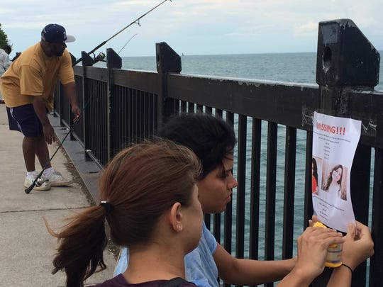 Grace Martinez's sister, Minda Martinez,  24, and Kristina Perry, 19, Grace's friend, tape up missing  flyers at Mariner Park on Detroit's east side at the Detroit River