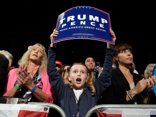 People cheer as Donald Trump speaks at a rally on