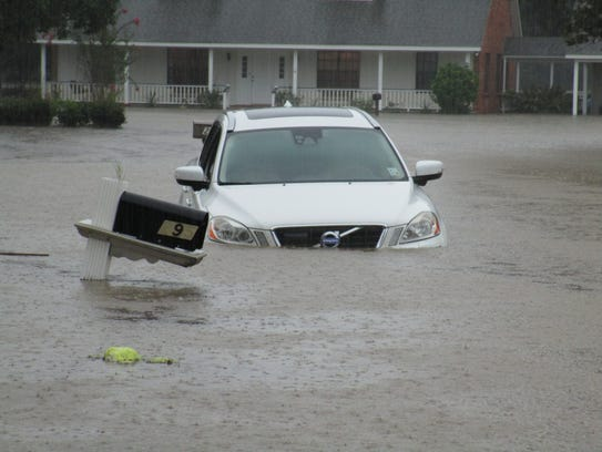 A car is submerged on a street near Comeax High School.