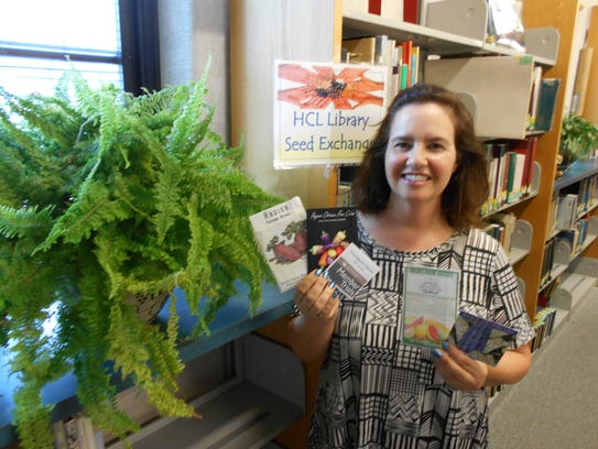 Reference Librarian Dana Neubauer shows seed packets
