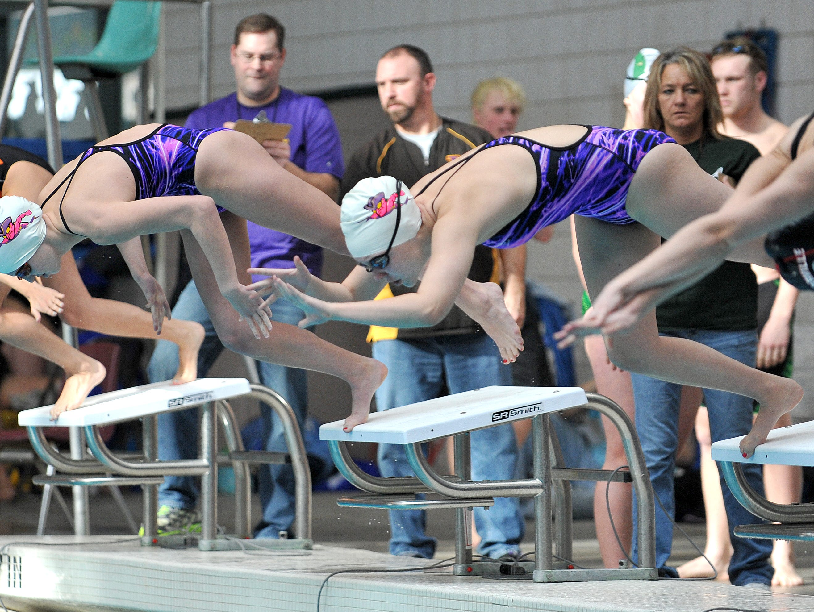 Lexington's Sammi Basinger (left) and 2015 grad Abbie Kaple compete in the 100 freestyle in last season's Ohio Cardinal Conference meet.