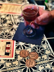 Tokens sit on a table collected by a customer while sharing drinks with friends at Coup, Tuesday, April 25, 2017, in New York. As a response to the Trump Administration, the bar in Manhattan's East Village offers patrons the chance to put their money where their politics are by earmarking where the profits should go from a range of liberal or progressive options like the American Civil Liberties Union or Planned Parenthood. Customers can drop the tokens in any of several labeled vases situated around the bar.