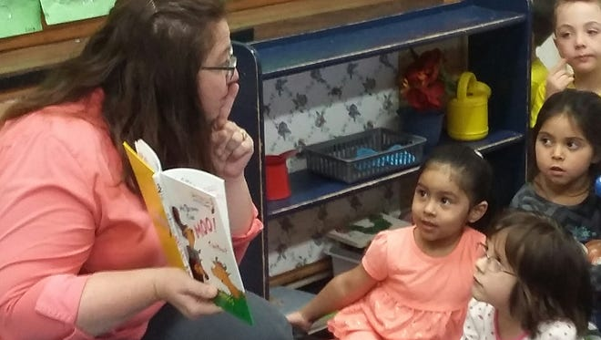 Employees from Domtar Corporation's pulp and paper manufacturing mill in Rothschild read books to children on April 27 at the Marathon County Head Start Program's Barrington Center in Wausau.