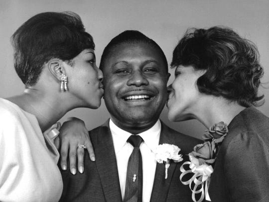 The Rev. C.L. Franklin gets a kiss on the cheeks from his daughters Aretha, left and Carolyn, right in 1965.