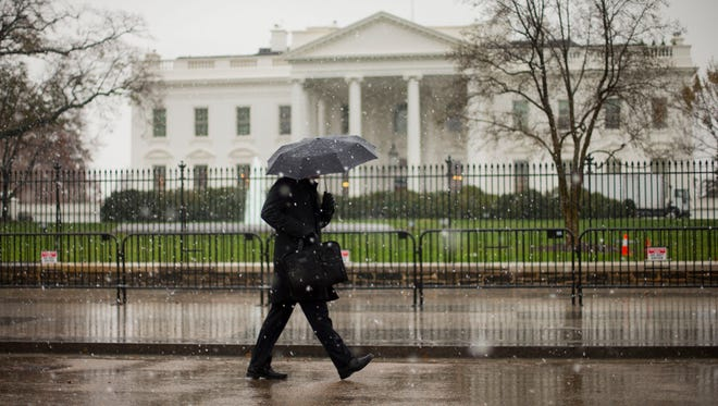 A pedestrian uses an umbrella to fend off a mix of snow and rain as he walks in front of the White House  Nov. 26.
