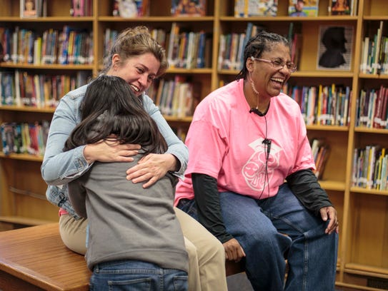Mentor Thersa Roberts, mentor, hugs Genesis Hernandez,