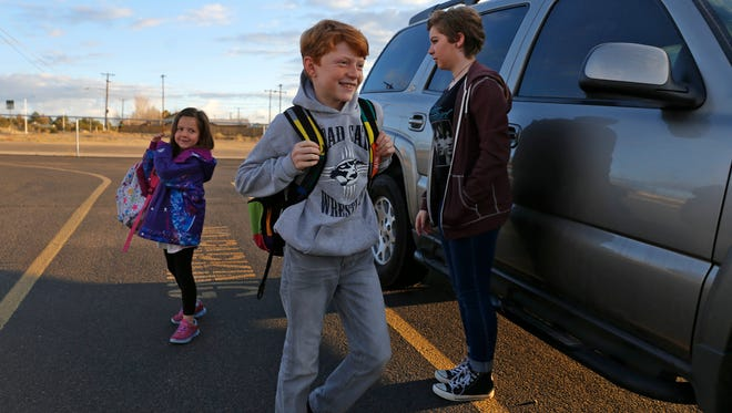 From left, Delaney Howlett and her brother Tylan Lovato are watched by their sister Ashleigh Lovato on Friday as they are dropped off at Country Club Elementary School in Farmington.