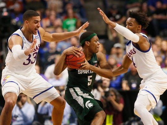 Michigan State guard Cassius Winston (5) is defended by Kansas forward Landen Lucas (33) and guard Devonte' Graham (4) during the first half of a second-round game in the NCAA men's college basketball tournament in Tulsa, Okla., Sunday, March 19, 2017. (AP Photo/Sue Ogrocki)