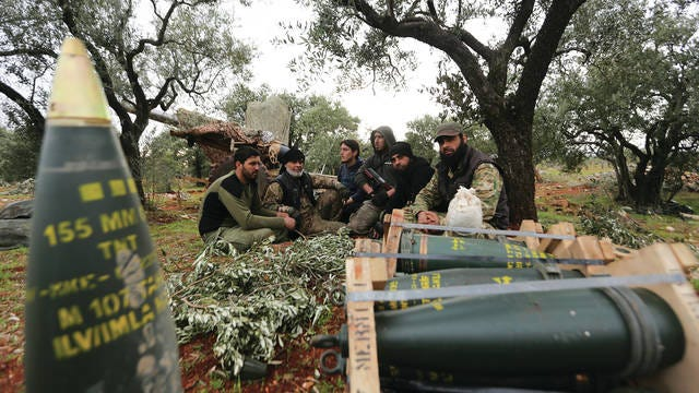 Turkish backed Syrian fighters take a break near the village of Neirab, in Idlib province, Syria, Monday.