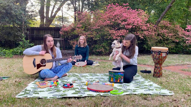 In this April 10 image from video, music therapists for St. Jude Children's Research Hospital, from left, Celeste Douglas, intern Abigail Parrish and Amy Love record a session in Love's backyard in Memphis. The group uploads their weekly sessions to YouTube so patients can continue receiving bedside music therapy.