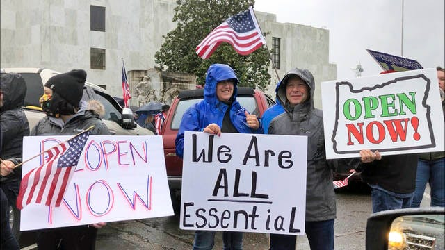 In this May 2 file photo, people hold signs protesting Oregon Gov. Kate Brown's executive order that shut down much of the state's economy and imposed social distancing, in her effort to stem the spread of the coronavirus, rally outside the Oregon State Capitol in Salem, Ore. A judge in rural Oregon on Monday tossed out statewide coronavirus restrictions imposed by Brown, saying she didn't seek the Legislature's approval to extend the stay-at-home orders beyond a 28-day limit.