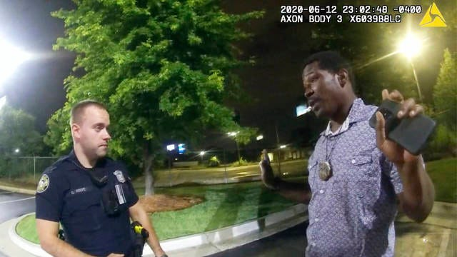 This screen grab taken from body camera video provided by the Atlanta Police Department shows Rayshard Brooks speaking with Officer Garrett Rolfe in the parking lot of a Wendy's restaurant, late June 12 in Atlanta. Rolfe has been fired following the fatal shooting of Brooks and a second officer has been placed on administrative duty.