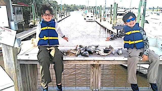 Young anglers James (left) and Alex Pugh of Richmond Hill are all smiles as they show this mixed catch that included several large croaker, all landed while fishing with Capt. David Newlin.