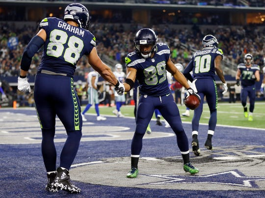 Seattle Seahawks' Jimmy Graham (88) congratulates Doug Baldwin (89) on his touchdown catch in the second half of an NFL football game against the Dallas Cowboys on Sunday, Dec. 24, 2017, in Arlington, Texas. (AP Photo/Ron Jenkins)