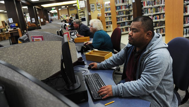Burt Kaious works at a computer while at the Sparks branch of the Washoe County Library System on April 25, 2015.