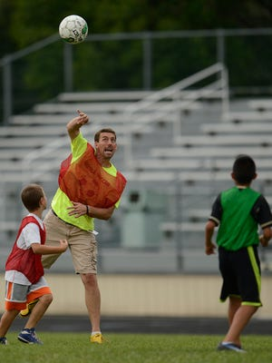 Green Bay Preble soccer coach Chris Becker has fun with kids. School won't be in session for a few weeks, but educators are gearing up to help cover costs.