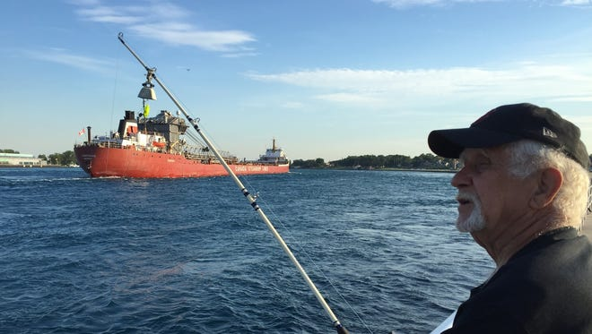 George McLeod, of Clyde Township, fishes for walleye as the freighter Frontenac heads downstream in the St. Clair River.