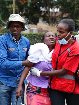 Kenya Red Cross staff help a woman after she viewed the body of a relative killed in Thursday's attack at Garissa University.