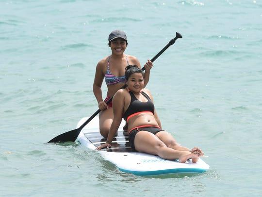 Cousins Rayann Joshua, 19, kneeling, Tasha Cruz, 17, take a ride on a paddle board in Merizo on Oct. 22, 2017.