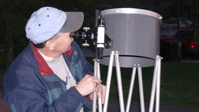 "Rod Martin of Tri-State Astronomers looks at the night sky through a large telescope. Club members will set up a variety of telescopes and assist viewers during Renfrew Institute's free ""star party"" on Thursday, December 8."